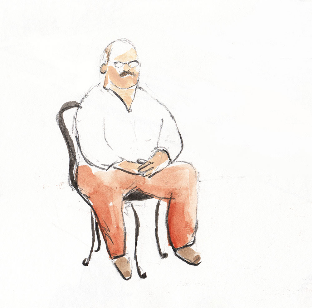 man with glasses sits on chair